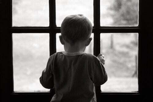 Bambino triste e solitario che guarda fuori dalla finestra.