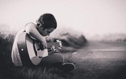 Ragazzino che suona la chitarra.