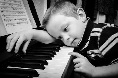 Bambino triste al pianoforte.