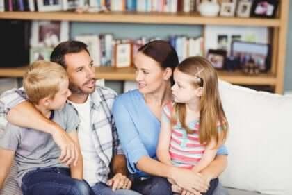 Essere genitori: famiglia parla seduta sul divano.