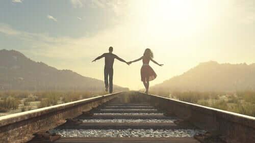 Coppia si tiene per mano sulle rotaie perché lo amore è un viaggio.
