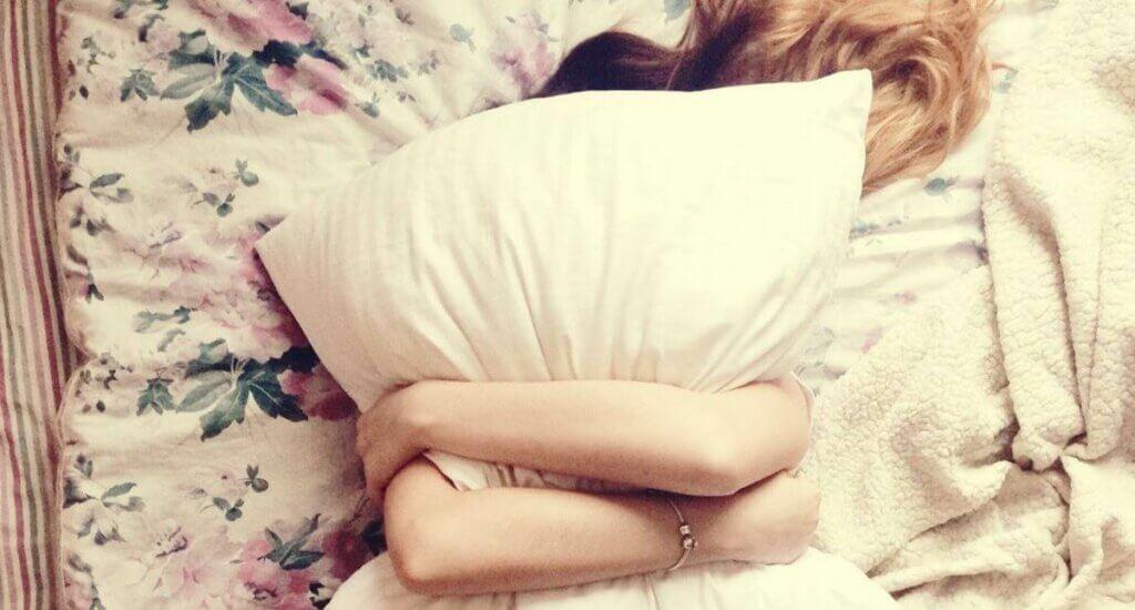 Donna abbraccia un cuscino.
