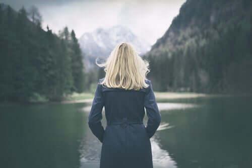 Donna di spalle guarda il lago.