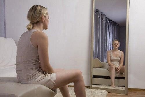 Donna che si guarda allo specchio.