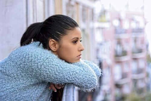 Donna che pensa affacciata al balcone.