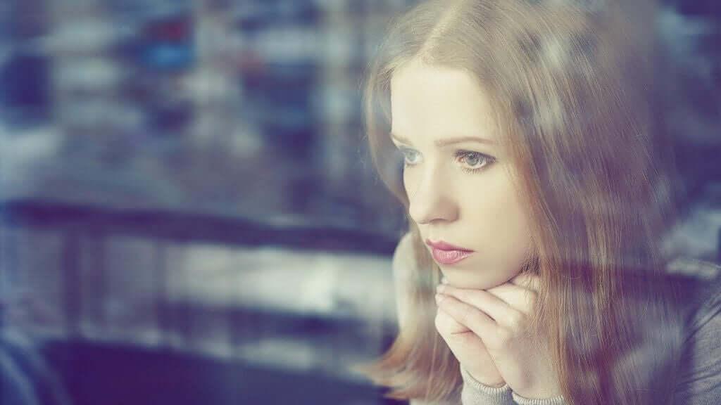 Donna triste guarda fuori dalla finestra.