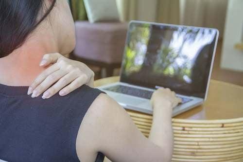 Donna con dolore al collo dalla postura con il computer.