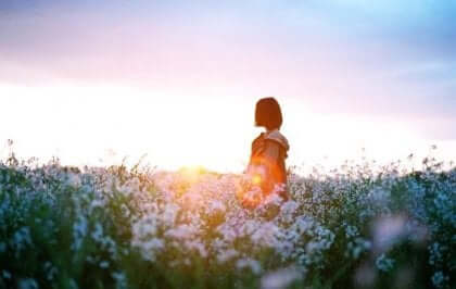 Ragazza ricerca il contrario della depressione in un campo di fiori.