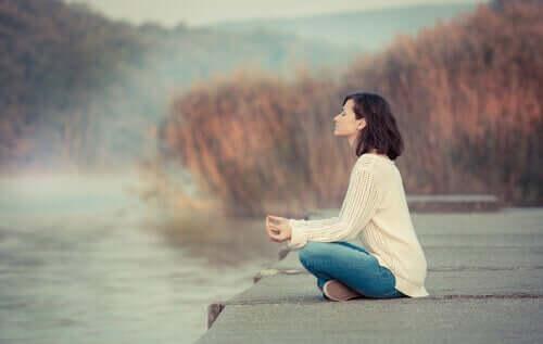 Ragazza medita in riva al lago.
