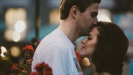 Uomo bacia la partner sulla fronte.