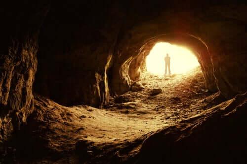 Uomo all'entrata di una caverna.