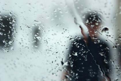 Silhouette di uomo dietro una finestra bagnata dalla pioggia.