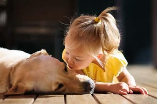 Bambina che bacia il suo cane.