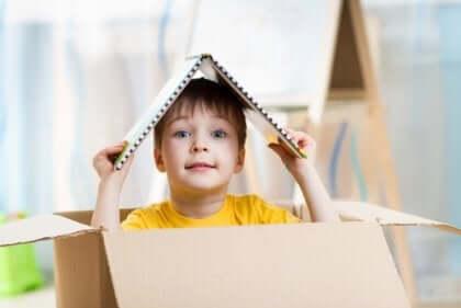 Bambino gioca dentro uno scatolone di carta.