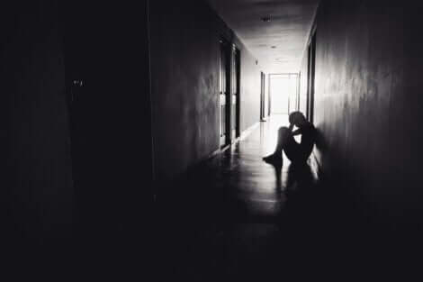 Bambino seduto a terra al buio.