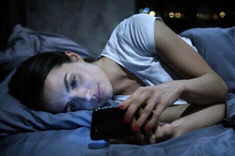 Innamorarsi a distanza e donna a letto guarda il cellulare.