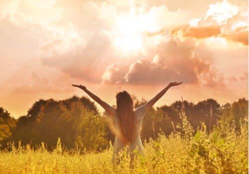 Ragazza in mezzo alla natura con le braccia aperte.