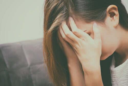 Donna che piange e che si copre il volto con le mani.