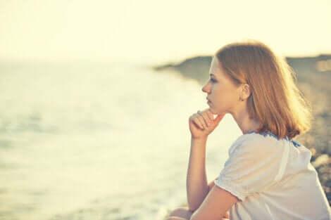 Donna pensierosa che guarda il mare.