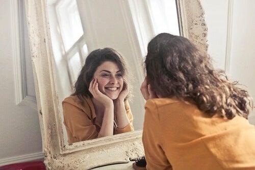 Donna che si guarda allo specchio sorridendo.