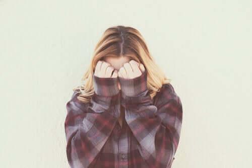 Donna timida che si copre il volto con le mani.
