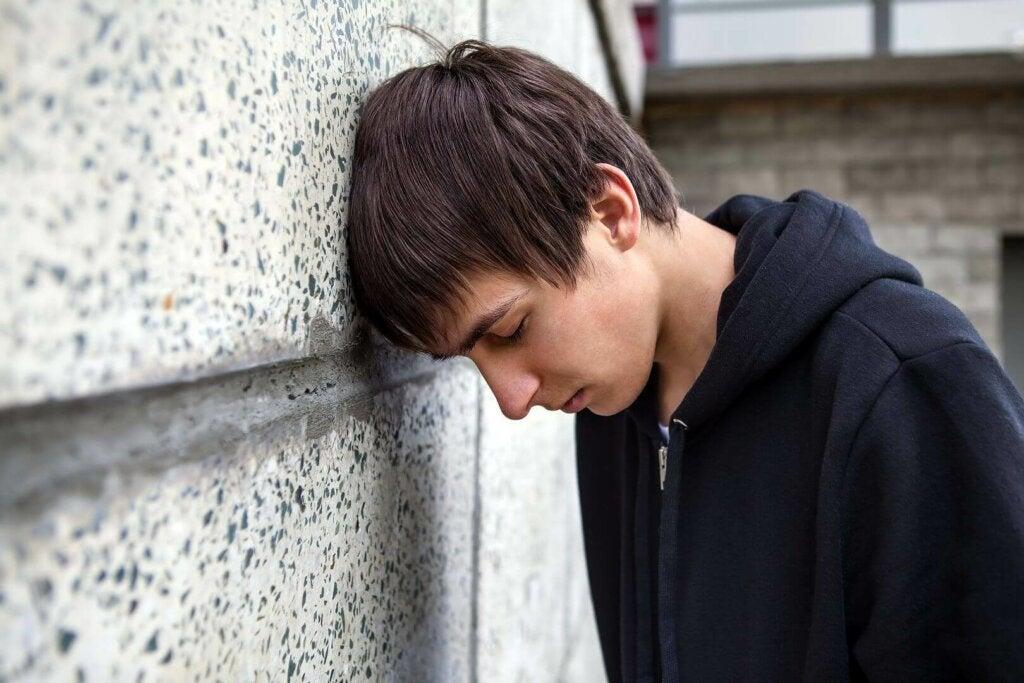 Figlio triste con la testa appoggiata al muro