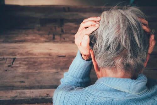 Paura del dolore, persona anziana con le mani alle tempie.