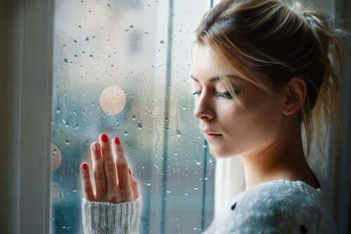 Ragazza triste alla finestra scaccia i pensieri negativi inconsapevoli.