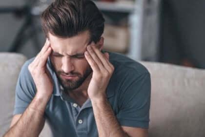 Uomo con mani sulle tempie per il mal di testa.