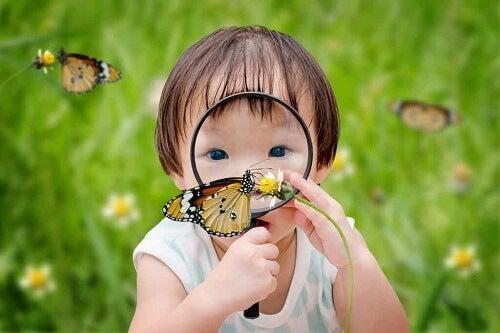 Bambina con lente di ingrandimento.