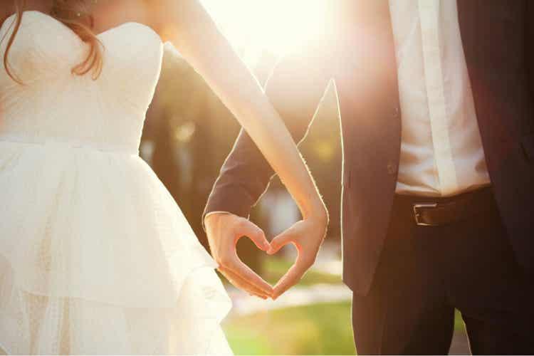 Coppia con mani unite a formare un cuore.