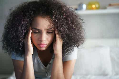 Donna con i capelli ricci riflette.