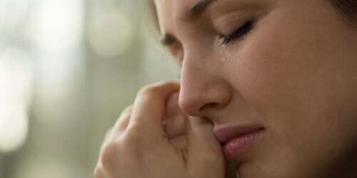 Donna che piange asciugandosi le lacrime.
