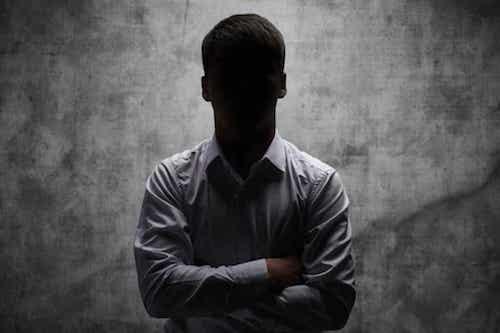 Persona in piedi con il volto nell'ombra.