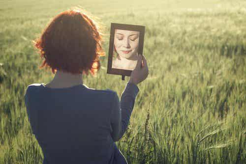 Ragazza si guarda allo specchio per conoscere se stessa ed essere felice.