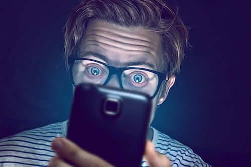 Uomo che guarda lo schermo del telefono.
