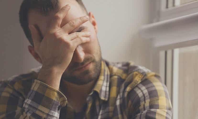 Uomo in atteggiamento di sofferenza psichica.