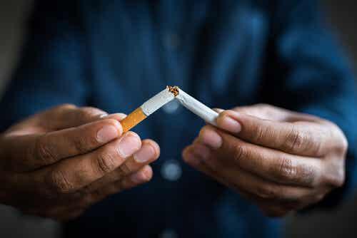 Uomo spezza sigaretta per combattere la cospirazione dell'industria del tabacco.