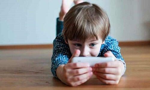 Bambino che gioca al cellulare.