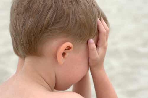 Bambino che si copre il viso con le mani.