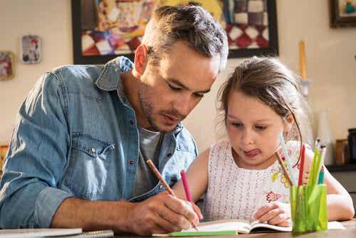 Padre e figlia che colorano insieme.