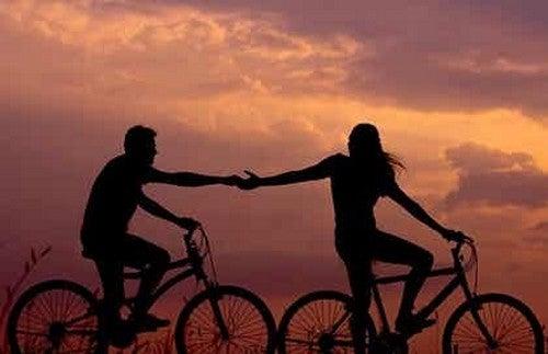 Tenersi per mano in bici al tramonto.