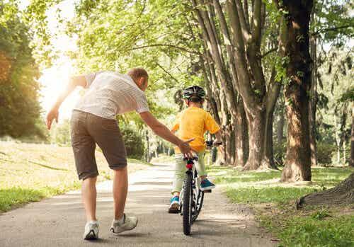 Padre che insegna al figlio ad andare in bicicletta.