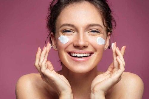 Donna che mette la crema sul viso.