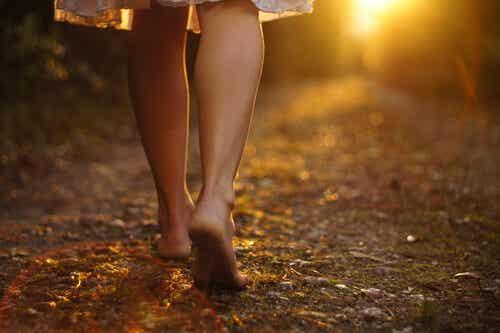 Donna che cammina a piedi scalzi lungo un sentiero di campagna.