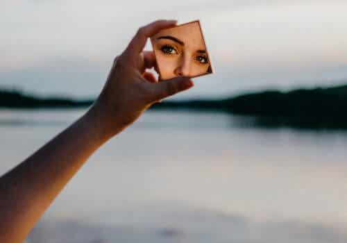 Donna che si guarda allo specchio vicino ad un lago.