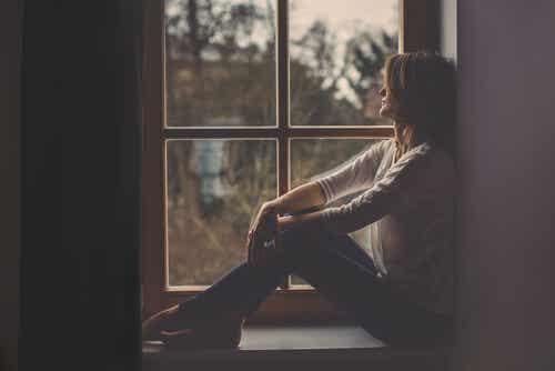 Donna che guarda dalla finestra e pensa di scrivere una lettera.