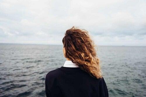 Ragazza di spalle davanti al mare.