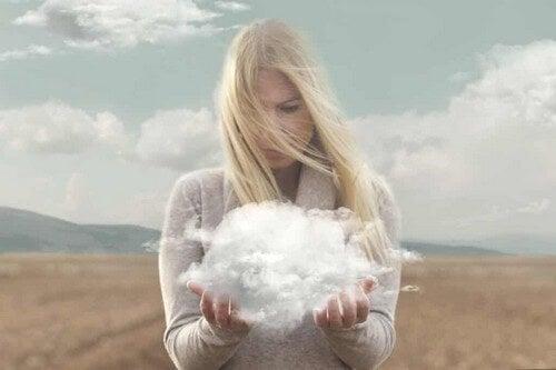 Donna tiene nuvole tra le mani.