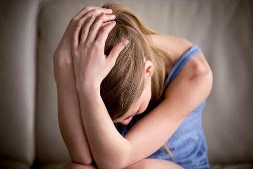 Donna che si regge la testa con fobie specifiche.